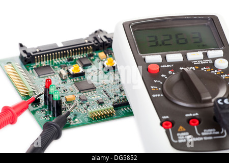 Digital multimeter and a circuit board isolated on white background - Stock Photo
