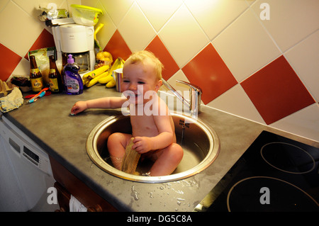 A baby having his bath and scrubbing his teeth in the kitchen sink - Stock Photo