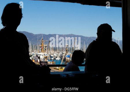 Bar patrons silhouetted with Santa Barbara Harbor in the background. - Stock Photo