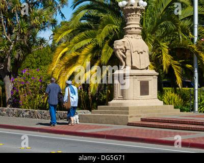 Elderly couple walking dog past elephant monument on Bridgeway in Sausalito, California - Stock Photo