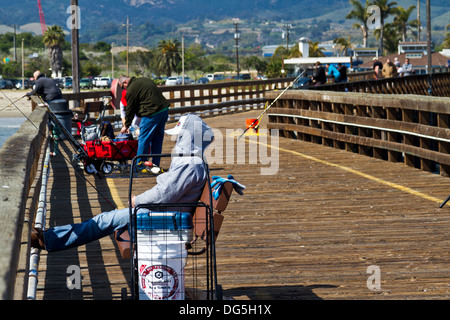 People fishing, relaxing, and strolling on a wooden pier in Goleta, near Santa Barbara, California. - Stock Photo