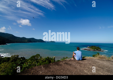 People at top belvedere enjoying the seascape view at Castelhanos Beach, Ilhabela, Brazil - Stock Photo