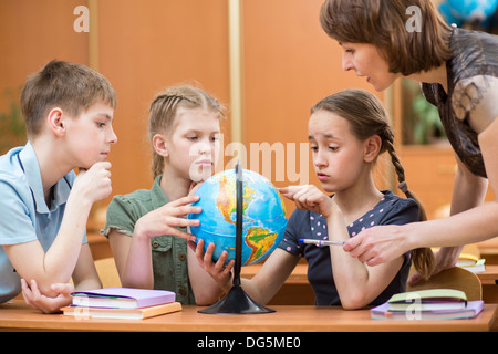 school kids studying a globe together with teacher - Stock Photo