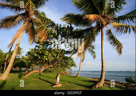 Young woman sitting at Las Galeras beach, Samana peninsula, Dominican Republic - Stock Photo