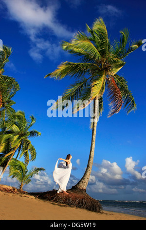 Young woman in white dress on a beach - Stock Photo