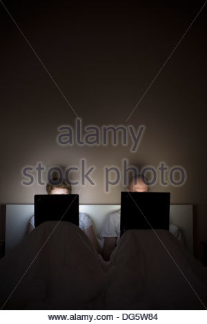 Young couple using laptops in bed - Stock Photo