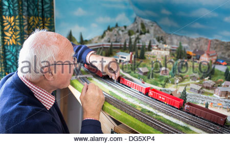 Senior man playing with toy train - Stock Photo