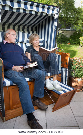 Senior couple sitting on a couch and reading books - Stock Photo