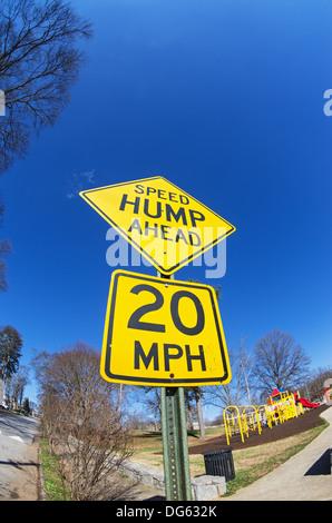 fisheye image of speed hump ahead sign with playground - Stock Photo