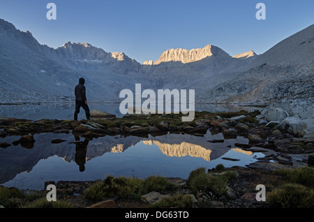 a man looking at the mountain morning view over Snow Lake to Mount Mills in the Sierra Nevada Mountains - Stock Photo