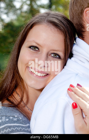 portrait of a happy young girl smiling, embracing her boyfriend - Stock Photo