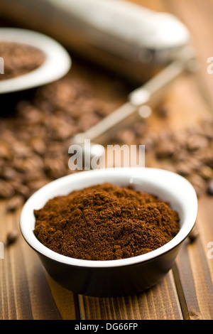 ground coffee in ceramic bowl on wooden table - Stock Photo