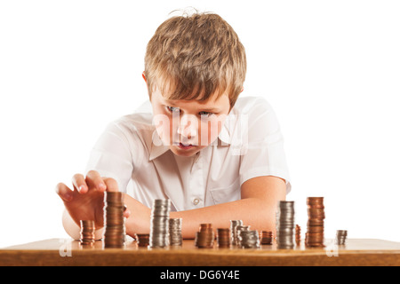 A young boy of 10 counts his money and stacks it up - Stock Photo