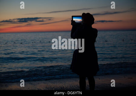 Aberystwyth Wales UK, October 15 2013  A woman using her tablet computer to photograph the dramatic skies at twilight - Stock Photo