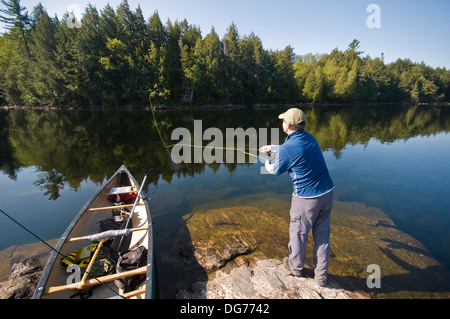 A man fly fishing from a canoe on little greenough pond in for Trout fishing ponds near me