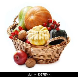 Fresh ripe pumpkins, apples, grape and nuts in wicker basket isolated on white - Stock Photo