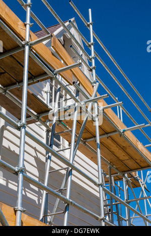 A low angle view of scaffolding against a two storey building undergoing repairs and renovations. - Stock Photo