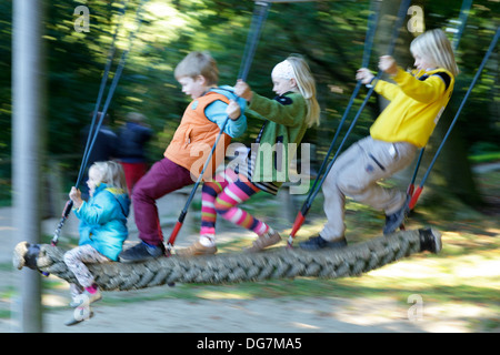 four children on a swing - Stock Photo