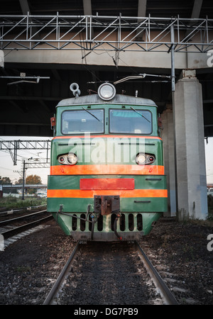 Green locomotive with red stripes on the cabin stands under the bridge on the railway - Stock Photo