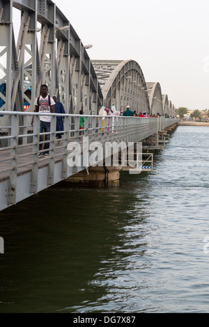 Senegal, Saint Louis. Pedestrians on the Pont Faidherbe, Bridge over the River Senegal. Built 1897. - Stock Photo