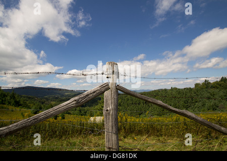 Old barbed wire fence set against a blue sky with scattered clouds in the mountains of North Carolina - Stock Photo