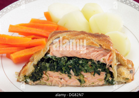 Salmon fillet stuffed with a spinach mixture and encased in puff pastry, served with boiled new potatoes and julienned - Stock Photo