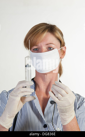 Nurse holding a syringe and wearing rubber surgical gloves - Stock Photo