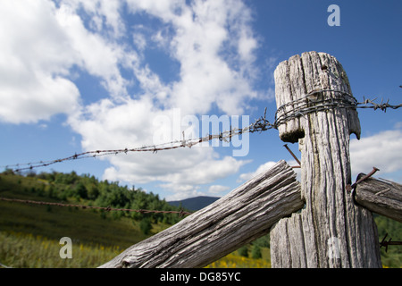 Old barbed wire fence and post against a blue sky with clouds in the mountains of North Carolina - Stock Photo