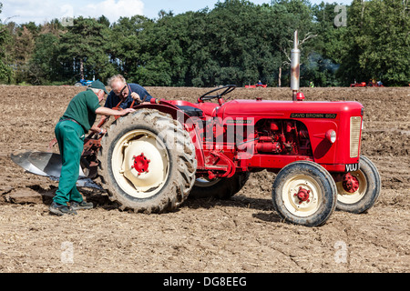 Red David Brown tractor with plough attachment - Stock Photo