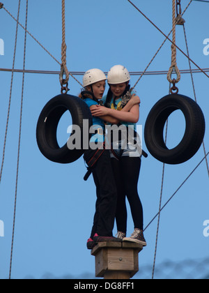 Two teenage girls standing on the top of a post looking scared, part of a adventure climbing frame, Bude, Cornwall, - Stock Photo