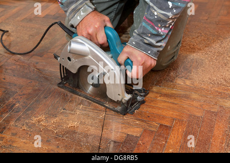 Worker cut old parquet floor with electric saw - Stock Photo