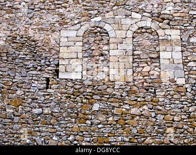 Espadaña de piedra sillar en un muro de mampostería de las ruinas del castillo almohade de Montánchez, fortaleza - Stock Photo