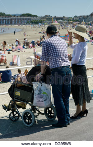 Older woman sat in a wheelchair, together with a younger man and woman all looking at the beach in Weymouth, Dorset, - Stock Photo