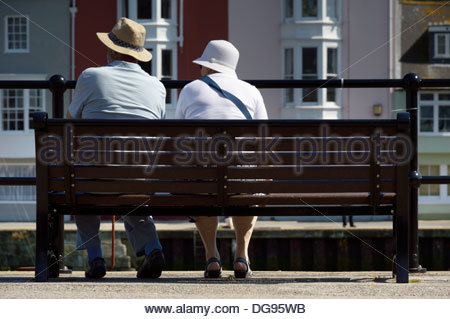 Older couple sitting on a bench overlooking the Harbour at Weymouth, Dorset, England - Stock Photo