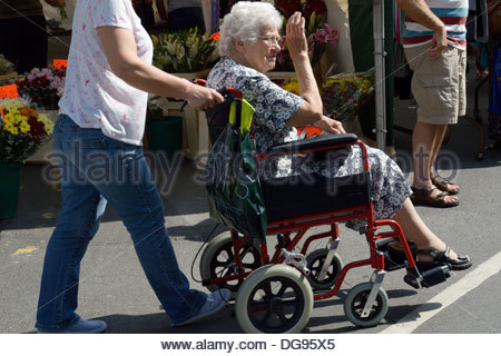 An elderly woman being pushed in a wheelchair - Stock Photo