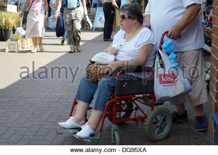 A older woman sitting in a wheelchair with her male carer - Stock Photo