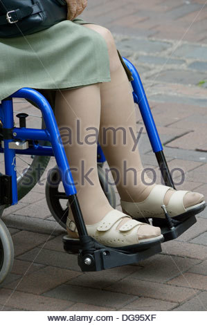 Close-up of the legs of an elderly woman sat in a wheelchair - Stock Photo