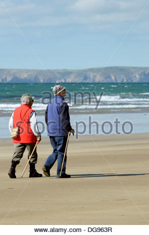 A couple walking with the aid of sticks on the beach at Broad Haven, Pembrokeshire, Wales, with St Brides Bay in - Stock Photo