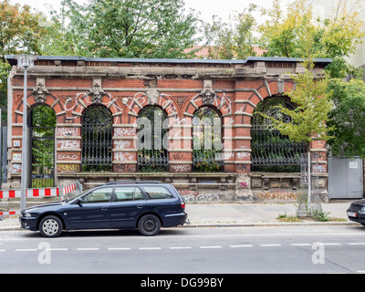 Section of red brick arched wall left in situ as part of property boundary - Stock Photo