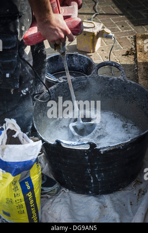 A workman mixing concrete render in a tub. - Stock Photo