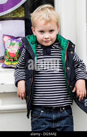 A three year old boy leaning against a shop window. - Stock Photo