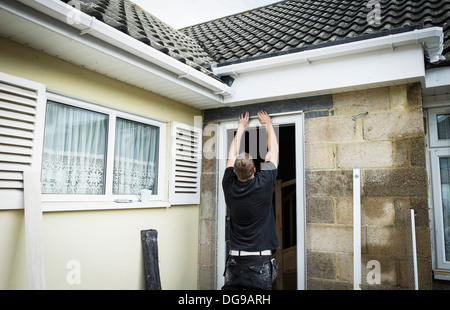 A workman fixing Render Stop Beading above a doorway. - Stock Photo