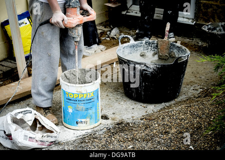 A workman mixing plaster in a bucket. - Stock Photo