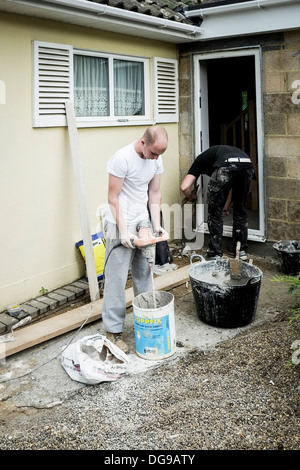 Plasterers working on a doorway to a house. - Stock Photo