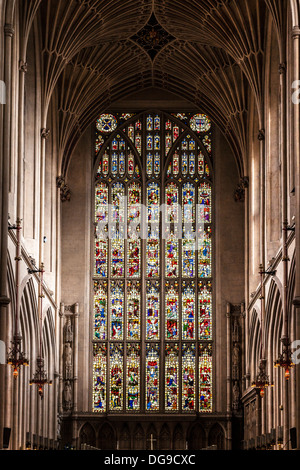 Interior of Bath Abbey showing the fan vaulting ceiling and stained glass window above the altar. - Stock Photo