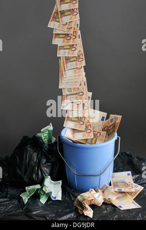Stream of money falls in a trash, Money Down The Drain - Stock Photo