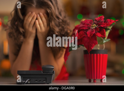 Closeup on phone and stressed woman in background - Stock Photo