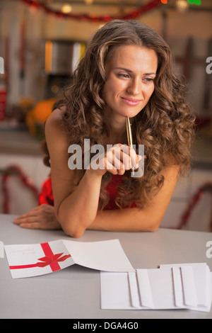 Thoughtful young housewife signing christmas postcards in kitchen - Stock Photo