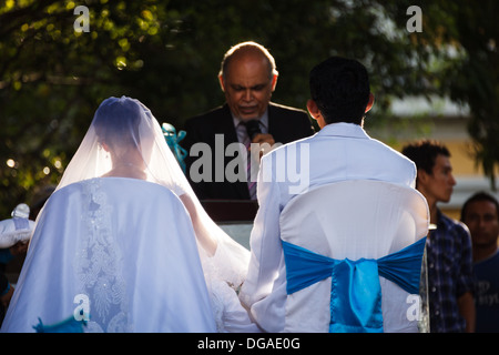 Young couple sitting in chairs in wedding clothes being married in the central plaza of Granada  in Nicaragua on - Stock Photo