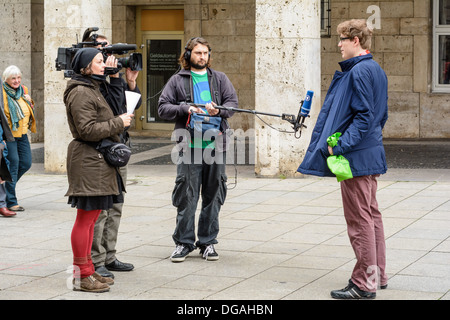 German television camera crew (ARD, WDR) interviewing a young Caucasian man on the street – Königstraße Stuttgart - Stock Photo